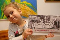 Kalendář v rukou drží tříletá Natálie Kasalová, jejíž prababička Vlasta Kasalová je zachycena na titulní straně skupinové historické fotografie.