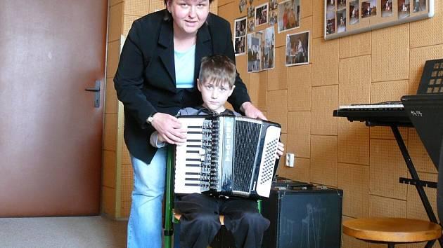 Na snímku vyučuje sedmiletého Davida Kruntoráda, který se učí na akordeon dva měsíce. Pod rukama své učitelky tichý chlapec roztává a pohotově hraje své první písničky.