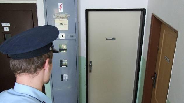 Policejní hlídka. Policista hlídkuje u bytu (dveře uprostřed) v jihlavském domě, kde došlo k vraždě.