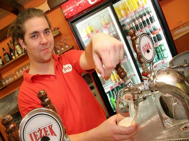 Pivo s úsměvem. Zaměstnanec Pivovarské restaurace v Jihlavě s úsměvem točí pivo pro své zákazníky. Poslední dny pro něj sice znamenají o hodně víc práce, ale optimismus neztratil.