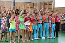 Slavnostní otevření nové tělocvičny v základní škole V Sadech zpestřili svým vystoupením (vpředu zleva) krasobruslařky, dívky z aerobik týmu SRC Fanatic, akordeonistka Markéta Laštovičková a za nimi třináct dívek z pěveckého souboru Oříšek.