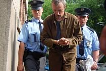 Eskorta odvádí zadrženého Slováka Antonína Nováka do hradecké vazební věznice.