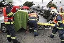Řidič v havarovaném automobilu, na jehož střeše uvízlo další auto. I s takovým úkolem si museli poradit hasiči v  rámci krajské soutěže ve vyprošťování.