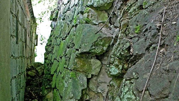 Kamení z poškozené zdi padá na garáže.