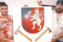 Dobrovolní hasiči v Uhelné Příbrami Jan Šrámek (vlevo) a Zdeněk Piskač si ve zbrojnici obecní znak přizdobili. Pod lva s bradaticí připevnili dvě hasičské sekerky.
