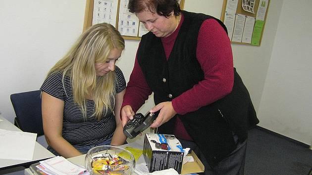 Speciální budík sluchově postiženého člověka upozorní nejen světelným signálem, ale i vibrací. To byla jedna z moderních kompenzačních pomůcek, které klientům poradny v rámci Týdne sociálních služeb představila Jiřina Kocmanová (vpravo).