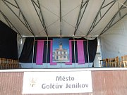 Pódium spozadím fota radnice Města Golčův Jeníkov.