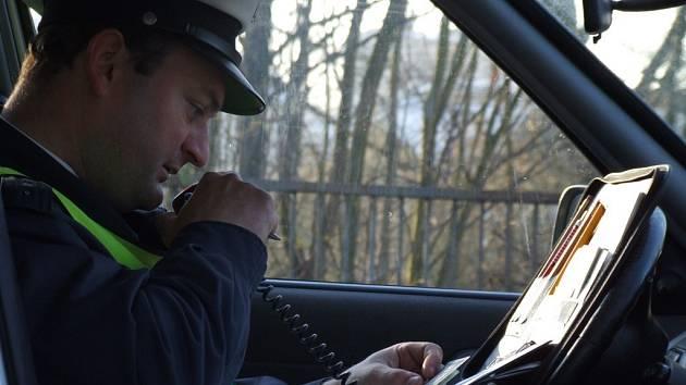 Prověření pachatele. Dopravní policista prověřuje totožnost řidiče, jehož automobil neměl registrační značku. Kvůli technickému stavu vozidla řidiči nebylo umožněno pokračovat v jízdě.