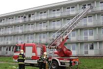 Pomocí vysokozdvižné plošiny a žebříku hasiči evakuovali tři uvězněné osoby ve čtvrtém patře budovy.