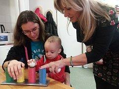 Vedoucí Střediska rané péče Irena Salaquardová (vpravo) předvádí možný nácvik jemné motoriky a pozornosti dítěte.