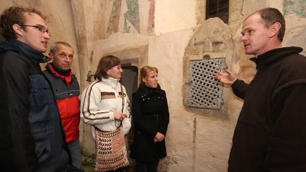 Kostel sv. Jiří v Řečici má sanktuárium z 12. století. Gorazd Cetkovský z řádu karmelitánů v Praze (vpravo) návštěvníkům Dne pro podlipnické kostely řekl, že nezná druhý příklad schránky pro uložení těla Páně z jednoho kvádru kamene.