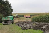 V popředí haldy bahna z rybníku, v pozadí sklízení kukuřice.