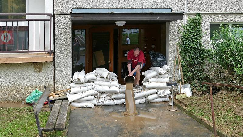 Úklid po řádění přívalových dešťů v zatopeném sídlišti Na Šancích v Chrudimi,