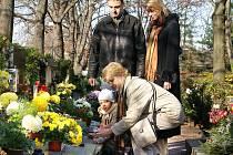 Dušičky jsou tady. Na hroby chodí položit květiny a věnce celé rodiny. Tato přišla dopoledne, ale pro někoho je lepší noc.