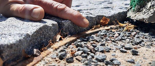 Vnové žulové dlažbě jsou už patrné vyjeté koleje od těžkých stavebních aut, kostky jsou křivě položené a do očí bijící je nesoulad vnivelitě skanalizačními poklopy. Patrné jsou išpatné dořezy betonové dlažby, nelícující spáry nebo úpravy jejich lemů.