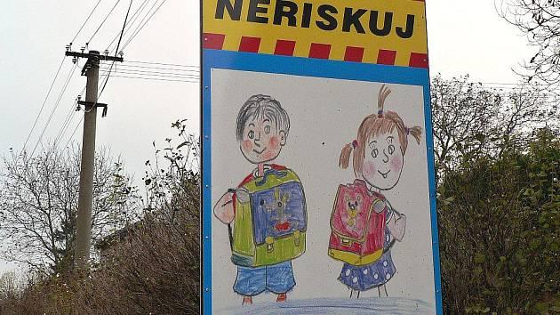 Cedule upozorňující řidiče v Holetíně.