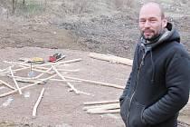 """Martin Kloda stojí před rozestavěným ohništěm, jež  tvoří létající  """"klacky"""". Nyní je už stavba dokončena."""