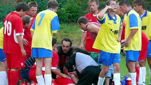 Na zemi leží zraněný obránce Dubský. Výmluvné je gesto jednoho z domácích hráčů: volejte sanitku!