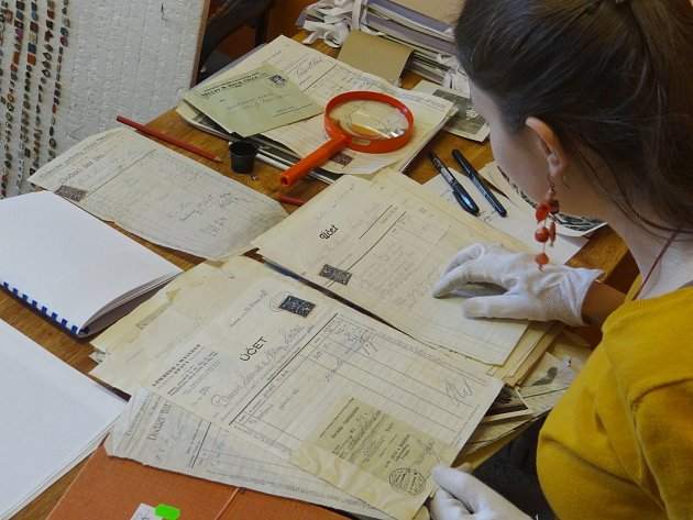 Věra Kuncová zařazuje nové přírůstky listiny a účty skutečských prvorepublikových firem.