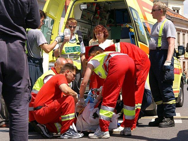 Záchranáři ošetřují chodce, který byl sražen u kruhové křižovatky Na Bídě v Chrudimi.