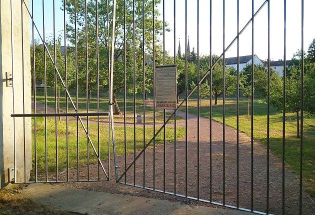 Pohled do Klášterních zahrad přes uzamčenou bránu