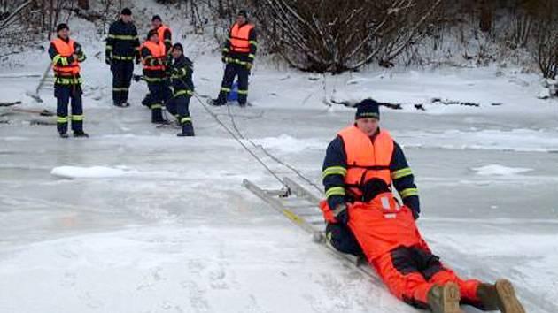 Hasiči nacvičují záchranu tonoucího z ledové vody.