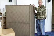 Nastěhovat volební místnost není těžké. Ladislav Bureš právě instaluje volební zástěnu z lehkého dřeva.