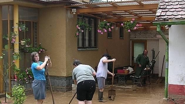 Lidé odklízejí nánosy bahna.
