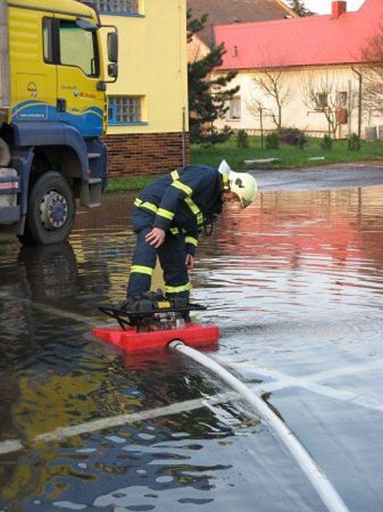 Hasiči bojují s vodou, která unikla při havárii potrubí v chrudimské Václavské ulici.
