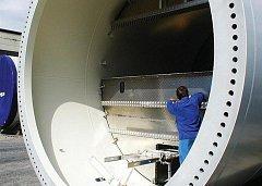 Technik provádí montáž uvnitř rozměrného tubusu budoucí větrné elektrárny.