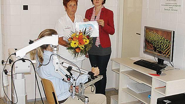 CERTIFIKÁT s předplatným jde do rukou lékařky, zatímco pacientka cvičí ruku na stroji Armeo.