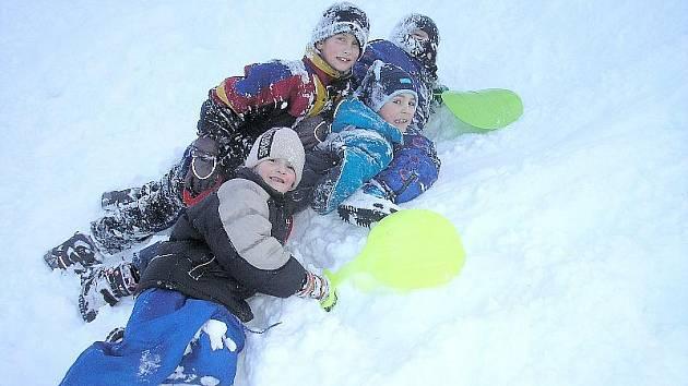Školáci si užívají zimních radovánek.