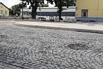 V nové žulové dlažbě jsou už patrné vyjeté koleje od těžkých stavebních aut, kostky jsou křivě položené a do očí bijící je nesoulad v nivelitě s kanalizačními poklopy. Patrné jsou i špatné dořezy betonové dlažby, nelícující spáry nebo úpravy jejich lemů.
