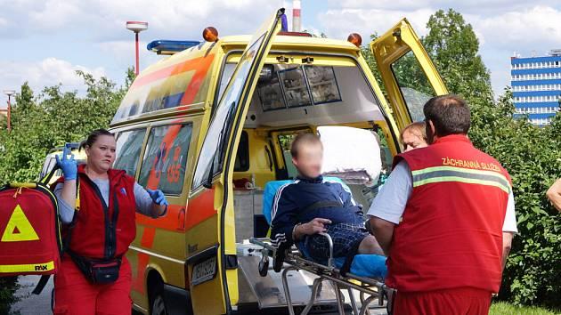 Záchranáři ukládají mladíka na lůžko, čeká ho převoz do specializovaného zdravotnického zařízení. Pár minut před tím mu lékařka aplikovala uklidňující injekci.