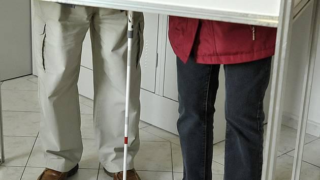 Vlastimila Kühra doprovází k volební urně manželka. Pomáhá mu také za plentou s vložením hlasovacího lístku do obálky.