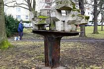 Rezivějícímu podstavci plastiky 'Transport síly' vévodí kameny pokryté mechem. Fontána chátrá opodál.