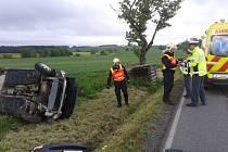 Automobil skončil po nehodě převrácený na boku v příkopu u silnice.