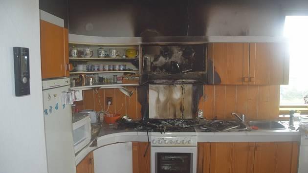 Plameny zasáhly digestoř, horní skříňky kuchyňské linky i dřevěný strop.