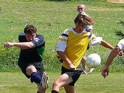 Sekretář fotbalistů TJ SSS Kočí Miroslav Raul přiihlíží souboji při utkání místního turnaje Kočí – Zaječice (v tmavém).