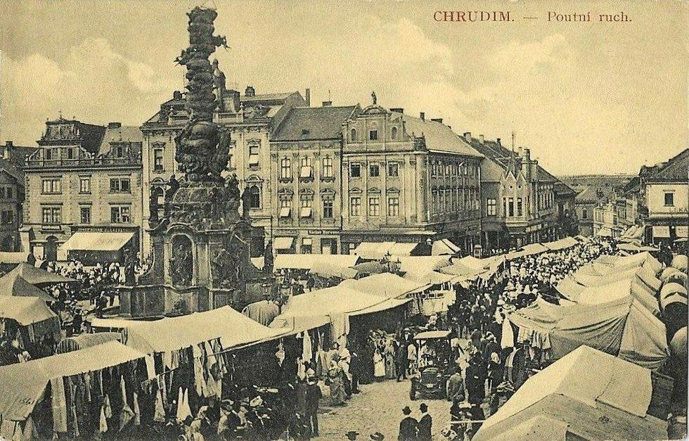 Poutní ruch na Riegrově náměstí v roce 1910.Mezi stánky prodejců projíždí jeden z prvních automobilů.