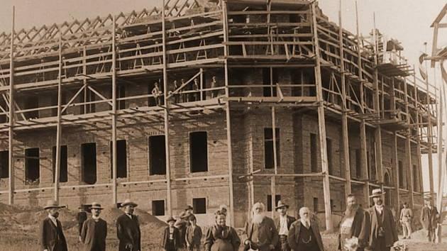 Na historické fotografii je kromě rozprostřené skupinky lidí rozestavěná budova hospodářské školy v Hlinsku. Snímek pochází někdy z roku 1907.