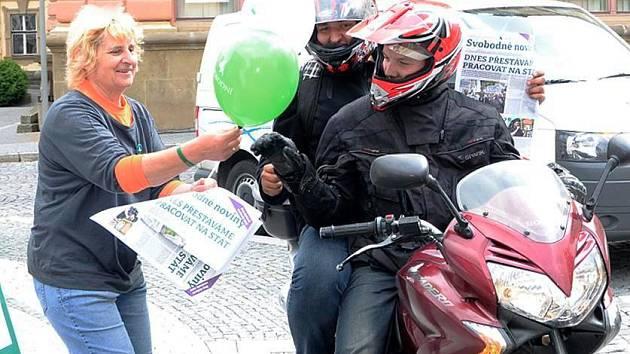 PROPAGAČNÍ tiskoviny a vzduchem plněné balonky si před Muzeem vyzvedla i dvojice mladých mužů na motorce.