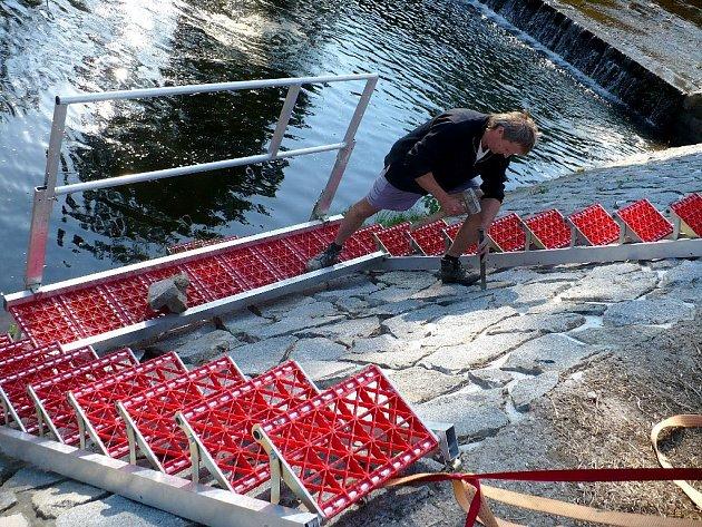 Petr Dubský ze státního podniku Povodí Labe provádí opravu vymletých spárů kamenného břehu Chrudimky u jezu v Janderově.