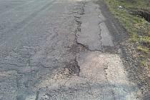 Rozbitý povrch silnice.