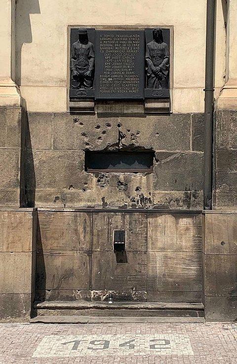 Působivá pamětní deska sochaře Františka Bělského z roku 1947 a palbou poškozené ventilační okénko vedoucí do krypty, jímž obléhatelé vháněli do interiéru vodu a slzný plyn.
