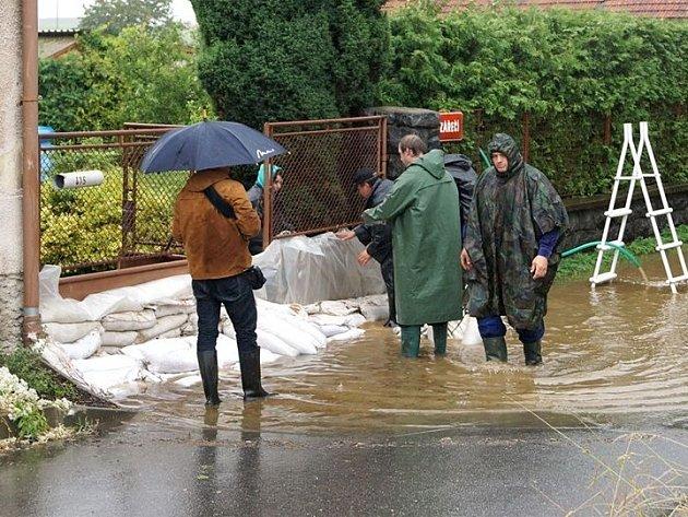 Novohradka v Luži se 25. června dostala na třetí stupeň povodňového ohrožení.. Lidé staví protipovodňové hráze za pomoci pytlů s pískem.