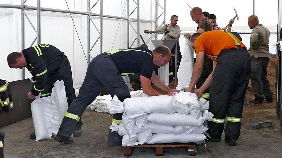 Novohradka v Úhřetické Lhotě začíná hrozit. V plné činnosti jsou hasiči z Chrudimi chystající pytle s pískem.
