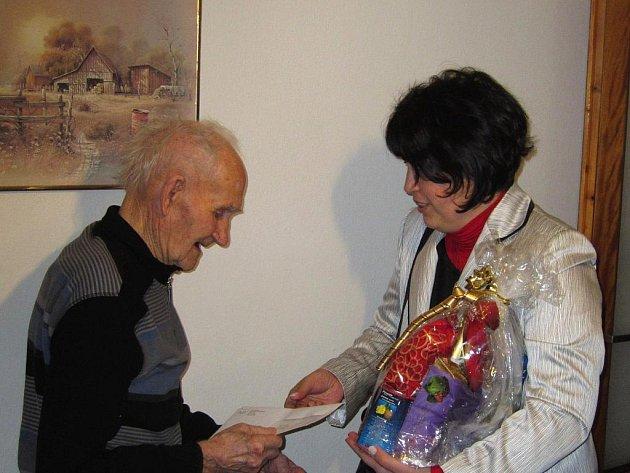Paní ředitelka ČSSZ Chrudim Blanka Urválková předává dar, dopis ministra a rozhodnutí o zvýšení důchodu.