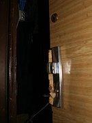 Poškozené dveře u jednoho z vykradených bytů.