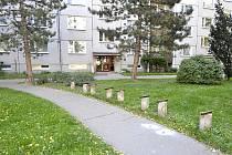 Rozebrané lavičky před bytovým domem.